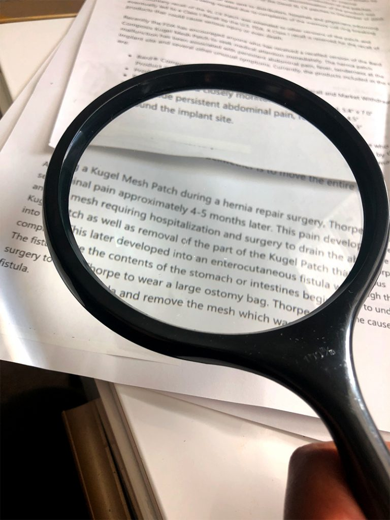 magnifying glass on medical records Palm Beach Legal Nurse